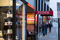 People walk past a fudge shop on Thames Street in Newport, Rhode Island, on Wed., April 19, 2017.