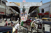 People transport textiles on rickshaws through chaotic traffic under an unfinished flyover on The Grand Trunk Road in Ludhiana.