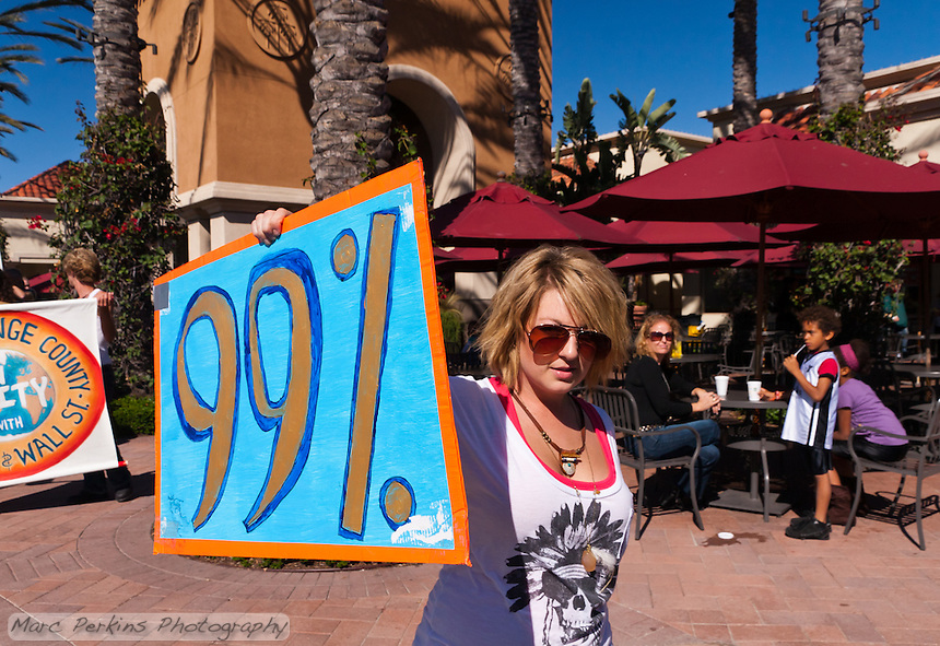 "Charlie proudly holds a ""99%"" sign while marching to the Bank of America branch in Irvine CA; behind her a family of three looks on.  At the Occupy Orange County, Irvine march on November 5."