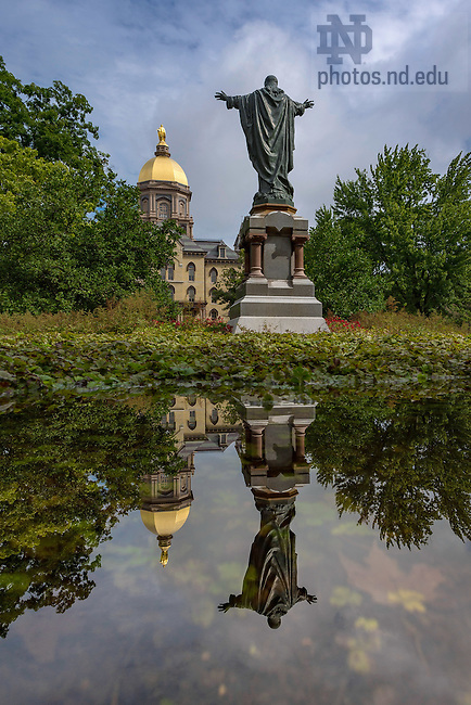 August 16, 2016; The Main Building and Sacred Heart Jesus statue are reflected in water collected in the flower bed around the statue after a record-setting rainfall. (Photo by Matt Cashore/University of Notre Dame)
