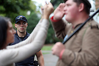 Police watch as Charlottesville resident Lara Rogers, left, confronts Allen Armentrout of North Carolina who stood wearing a Confederate outfit with 2 guns protecting the Lee Statue Tuesday, Aug. 15, 2017 at Emancipation Park in Charlottesville, Va. A small crowd of Charlottesville residents protested him for 30 minutes before Police escorted Armentrout away from the park. Photo/Andrew Shurtleff