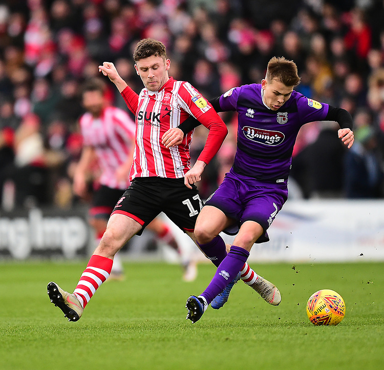 Lincoln City's Shay McCartan vies for possession with Grimsby Town's Jake Hessenthaler<br /> <br /> Photographer Andrew Vaughan/CameraSport<br /> <br /> The EFL Sky Bet League Two - Lincoln City v Grimsby Town - Saturday 19 January 2019 - Sincil Bank - Lincoln<br /> <br /> World Copyright &copy; 2019 CameraSport. All rights reserved. 43 Linden Ave. Countesthorpe. Leicester. England. LE8 5PG - Tel: +44 (0) 116 277 4147 - admin@camerasport.com - www.camerasport.com