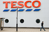 Young man with a mobile phone walks past a Tesco store in Vauxhall, London.