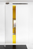 A flush white kitchen cupboard, behind which is concealed a sink in a vibrant yellow recess.