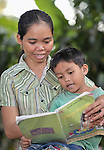 Nob Chan helps her son Nhouv Visal, 6, with his homework in Khnach, a village in the Kampot region of Cambodia.
