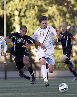 Boston College midfielder/defender Dylan Pritchard (14) brings the ball forward as Brown University midfielder Daniel Taylor (19) challenges. Brown University (black) defeated Boston College (white), 1-0, at Newton Campus Field, October 16, 2012.