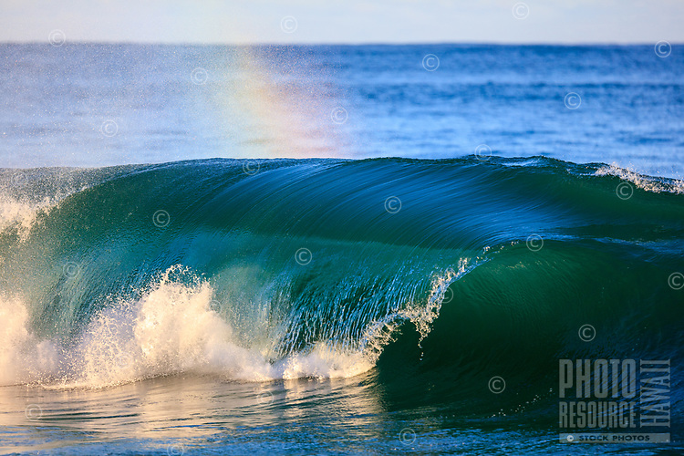 A glassy blue-green wave breaks with a heavy lip as rainbow appears in the spray at Lumahai Beach, Kauai.