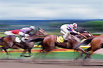 Horse Race with riders and horses bunched up at the finish line using a slow shutter speed for motion.