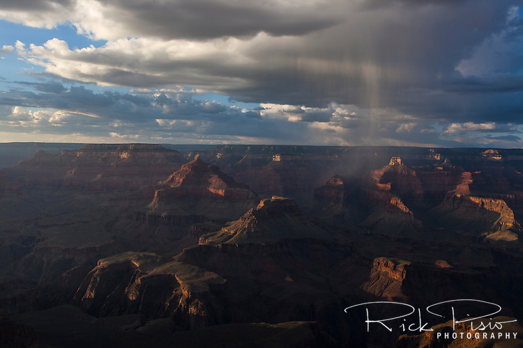 A rain squall passes over the Grand Canyon at sunset.