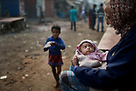 An elderly man sits his granddaughter by the side of a road early morning in Dhaka, Bangladesh.