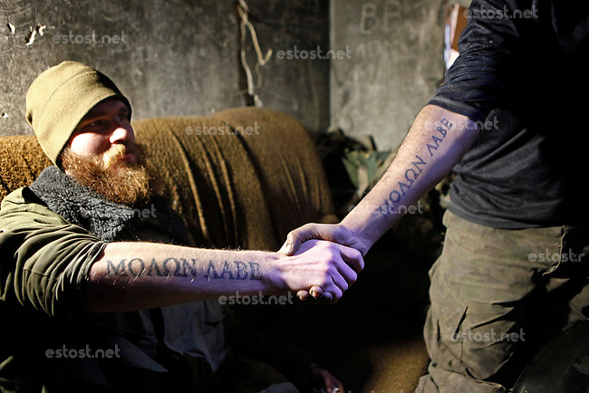 "UKRAINE, 02.2016, Oblast Donetsk. Ukrainian-Russian conflict concerning Eastern Ukraine / Foreign volunteers (""Task Force Pluto"") fighting with the far-right militia Pravyi Sektor against the Russian-backed separatists: Craig (USA) and Ben (Austria) pose with the jointly tattooed Greek quote ""Molon Labe"" (come and take them) on their arms. © Timo Vogt/EST&OST"