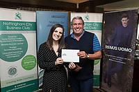 Denada Berisha of Remus Uomo gives a raffle prize to John Parkhouse