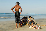 NgweSaung beach resort, a fisherman stands over the nights catch as women weigh the fish caught. Burma Myanmar 2011
