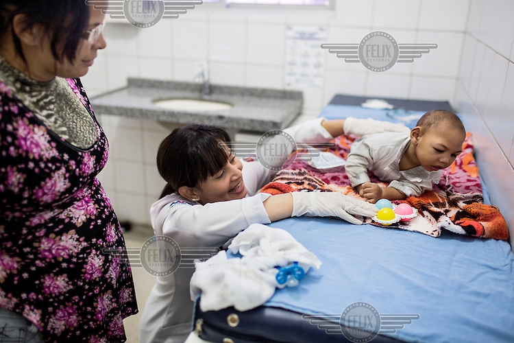 Speech therapist, Danielle Oliviera meets with nine-month-old Alexandre de Carvalho, who was born with Zika-related microcephaly, and his adopted mother, Silvana de Carvalho, 40, left, at Oswaldo Cruz University Hospital. Ms. Oliviera rattles a toy around the baby so he can try to follow the sound to stimulate movement.
