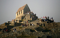 People tour the ruins of the Machu Picchu guard house near Aguas Calientes, Peru, on May 18, 2008. Machu Picchu, often referred to as the ?Lost City of the Incas,? is a pre-Colombian Inca site situated on a mountain ridge above the Urubamba Valley. Visits to Peru?s top tourist destination have more than doubled in the last decade to 800,000 people.