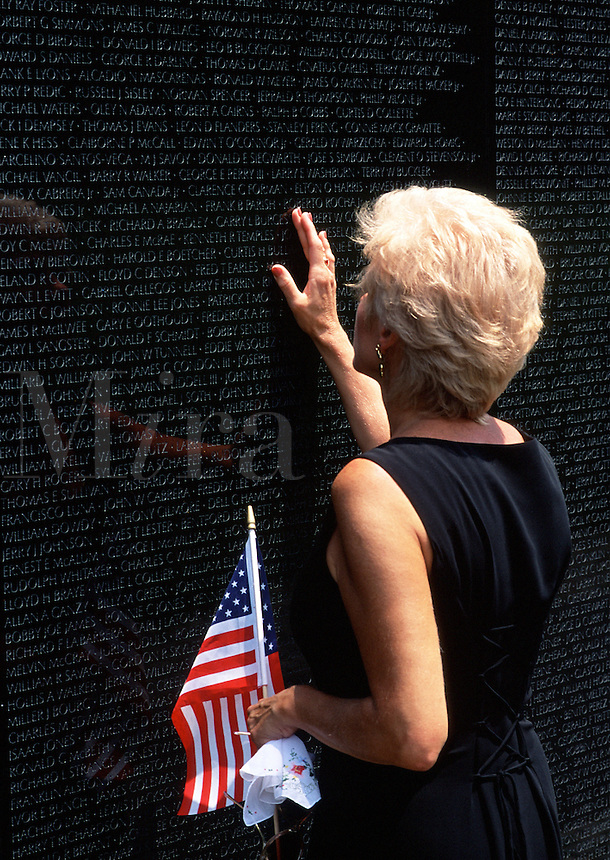 A woman holds an American flag as she mourns her dead at the Vietnam War Memorial. Washington, DC.
