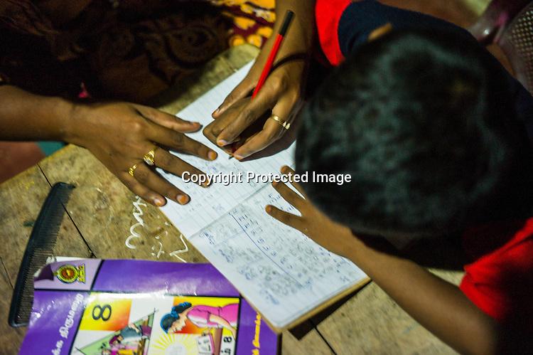 Mathumita tutors her son after long day of work at her mother's house in Punaineeravi village in Kilinochchi in Northern Sri Lanka. Photo: Sanjit Das/Panos