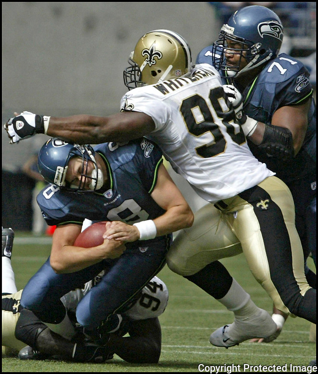 Seahawks' quarterback Matt Hasselbeck is sacked by Saints' defenders Charles Grant (94) and Willie Whitehead (98) during the second quarter on Sunday, Sept. 7, 2003 at Seahawks' Stadium. Even through being sacked, Hasselbeck completed 12 of 23 passes for 137 yards and two touchdowns, leading the Seahawks over the Saints 27-10. (AP Photo/Jim Bryant)