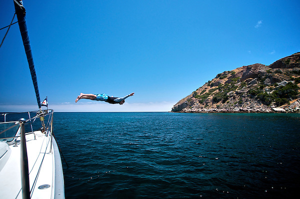 Man diving off the bow of a sailboat near the shores of Catalina Island, California.