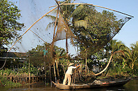 Nguyen Bao Linh is lifting his net with the help of his son and allow a boat to pass the narrow canal. Truong Thanh village, Can Tho province, Mekong delta, Vietnam-2010