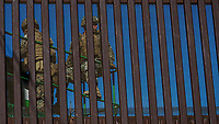 "MEXICALI,  MEXICO - November 26. US army soldiers are seen through the wall US-Mexico border wall while working on the installation of barbed wire on top of the wall on November 26, 2018 in Mexicali, Mexico.<br /> The U.S. government said it was starting work to ""harden"" the border crossing  Mexico, to prepare for the arrival of a migrant caravan leapfrogging its way across western Mexico. For the Trump administration and those who support the president's hard-line stance on illegal immigration, the chaos illustrated what they long have feared. For others, the images of the Border Patrol using tear gas on a group of migrants that included children were deeply disturbing (Photo by Luis Boza/VIEWpress)"