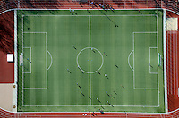 Billtalstadion: EUROPA, DEUTSCHLAND, HAMBURG, BERGEDORF (EUROPE, GERMANY), 26.02.2012: Fussballfeld, gespielt wird auf einem rechteckigen Feld, das eben und frei von Hindernissen ist. Normalerweise besteht der Bodenbelag im Profifußball aus Rasen, seltener wird auf einem Hartplatz oder Kunstrasenplatz gespielt..Die Laenge der kurzen Seiten (Torlinie, faelschlicherweise auch Grundlinie) muss bei nationalen Spielen zwischen 45 und 90 Meter, die der langen Seiten (Seitenlinie) zwischen 90 und 120 Meter betragen. Die sich in der Theorie ergebende Moeglichkeit eines annaehernd quadratischen Spielfeldes (Seitenlinie zwingend laenger als Torlinie) kommt in der Praxis nicht vor. Ueblich sind 68 mal 105 Meter wegen der in Leichtathletikstadien umlaufenden 400-m-Kunststoffbahn mit 100-m-Gerade parallel zur Seitenlinie. Diese Spielfeldgroesse muss in einigen Europacupwettbewerben und seit 2008 auch bei Laenderspielen exakt eingehalten werden..Das Spielfeld wird in der Regel durch weiße Linien (meist Kalk oder Farbe) markiert. Bei beschneitem Boden koennen die Linien aus einem dunklen Material aufgebracht werden.  Alle Linien muessen gleich breit sein, die zulaessige Breite der Linien betraegt maximal zwoelf Zentimeter. Eine Mindestbreite fuer die Linien ist nicht ausdruecklich vorgeschrieben, allerdings muss die Erkennbarkeit hinreichend gegeben sein, so dass faktisch eine Breite von fuenf bis sechs Zentimetern nicht unterschritten werden darf. .Das Billtalstadion ist ein Sportplatz in der Freien und Hansestadt Hamburg im Stadtteil Bergedorf. Es bietet rund 30.000 unueberdachte Plaetze wovon jedoch nur 300 Sitzplaetze sind. Das Billstadion wurde 1950 erbaut. Erst 2009 begann eine grundlegende Sanierung der Anlage. Der Grandplatz wurde durch einen Kunstrasen ersetzt, ausserdem fand eine Modernisierung der Sitzbaenke, Treppen, und der Flutlichtanlage statt. Eine Besonderheit dieses Stadions ist, dass das Spielfeld und die Aschenbahn in einer Senke liegen, waehrend die Zuschaue