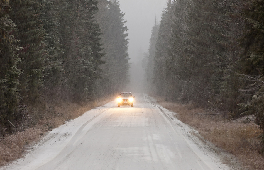 A single car with its headlights on drives down a road during a snow storm.