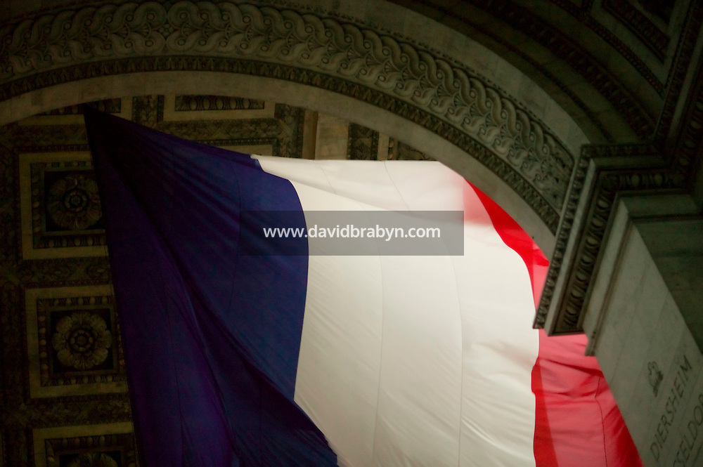 A giant French Tricolore flag flies under the Arc de Triomphe in Paris, France, 13 July 2007, ahead of the celebrations of Bastille Day on the 14th.