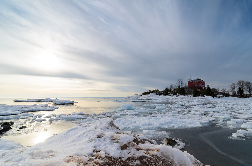 An icy morning view of the Marquette Harbor Lighthouse with interesting clouds and sun on the last day of March. Marquette, MI