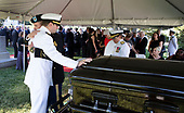 In this hand-out photo released by the McCain family, Jimmy McCain hugs his brother Jack McCain, touching casket, as Cindy McCain, watches during a burial service for Sen. John McCain, R-Ariz.,at the cemetery at the United States Naval Academy in Annapolis, Md.  <br /> Credit: David Hume Kennerly / McCain Family via CNP