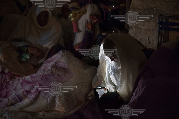 A woman reads religious scripts by torch light as Christian pilgrims gather in the Ethiopian section of the Church of the Holy Sepulchre for the Holy Fire ceremony during Easter.