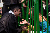 A graduating student talks through the fence separating family and friends from the graduating class during the 2012 MIT Commencement on June 8, 2012, in Cambridge, Massachusetts, USA...Photo by M. Scott Brauer
