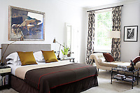 In this stylish bedroom the double bed is dressed with a pair of gold coloured cushions and a grey blanket with red trim