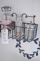 A small selection of vintage inspired bottles  is displayed in a wire container on the bathroom wall