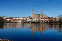 General view, Cathedral, Salamanca, Spain, pictured on December 18, 2010 in the afternoon, with the Bell Tower and Cupola towering over the surrounding houses, and reflected in the Tormes river. Salamanca, Spain's most important University city,  has two adjoining Cathedrals, Old and New. The old Romanesque Cathedral was begun in the 12th century, and the new in the 16th century. Its style was designed to be Gothic rather than Renaissance in keeping with its older neighbour, but building continued over several centuries and a Baroque cupola was added in the 18th century. Restoration was necessary after the great Lisbon earthquake, 1755. Picture by Manuel Cohen