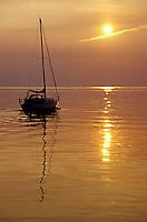 421-111 Sailboat leaving Ellison Bay under motor power at sunset over Green Bay, Lake Michigan