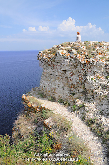 "Girl sitting on a rock of Devia hill and observing Volga reservoir in Russian National Park ""Samara Luka"""