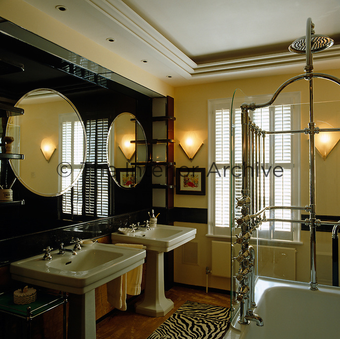 A pair of wash basins stand beneath round mirrors mounted on a polished black stone wall and the shower features an elaborate chrome shower and taps