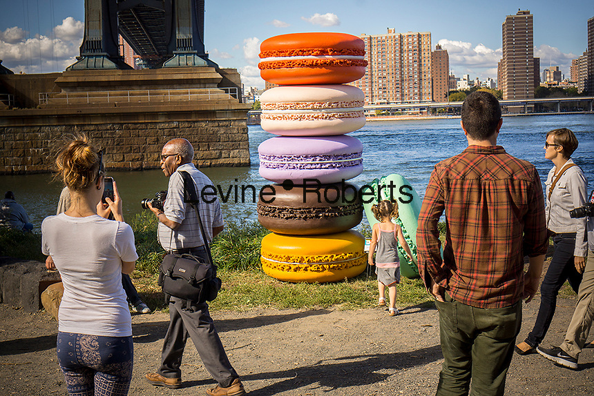 """Visitors to the Brooklyn neighborhood of Dumbo interact with """"Macaron"""" by the artist Daisuke Kiyomiya during the annual Art Under the Bridge Dumbo Arts Festival on Saturday, September 28, 2013.  Dumbo has been a neighborhood shared by industry and artists but high real estate prices have created opportunities for development with the subsequent increase in rents.  (© Richard B. Levine)"""