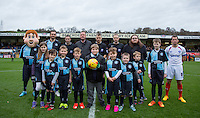 Mascots & Matchball sponsors pose with captains Paul Hayes of Wycombe Wanderers & Michael Doyle of Portsmouth & Referee Mark Haywood & his assistants during the Sky Bet League 2 match between Wycombe Wanderers and Portsmouth at Adams Park, High Wycombe, England on 28 November 2015. Photo by Andy Rowland.