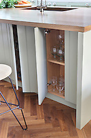 Detail of a kitchen cupboard with a veneered interior to match the oak worktop and flooring