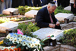 Israel's Prime Minister Benjamin Netanyahu lights a candle by his brother Yonatan's tomb during a memorial ceremony at Mount Herzl military cemetery in Jerusalem. Yonatan Netanyahu was killed while leading the 1976 raid to rescue hijacked Israeli hostages from Entebbe, Uganda.