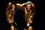 (R) Wong Ka Chun and (R) Wong Man Pan flexes muscles for judges on stage during the Hong Kong Bodybuilding Championship on 29 June 2014 at the Queen Elizabeth Stadium Arena in Hong Kong, China. Photo by Aitor Alcalde /  Power Sport Images