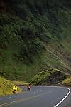 Bike riders wearing rain coats along Highway 101 southern coast Oregon State USA
