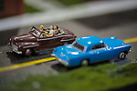 Hicksville, New York, USA. February 22, 2015. A blue classic model car and brown model car with driver and passengers are in road scene display at the Model Train Exhibit is hosted by Trainville Hobby Depot at the Broadway Mall, including an N Scale layout, the Long Island HOTrack train club HO scale model train portable modular layout, and others. Donations were accepted at exhibit to support the Nassau County Empire State Games for the Physically Challenged.
