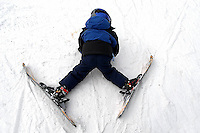 A young boy works to stand up on skis at Sugar Mountain Ski Resort in NC.