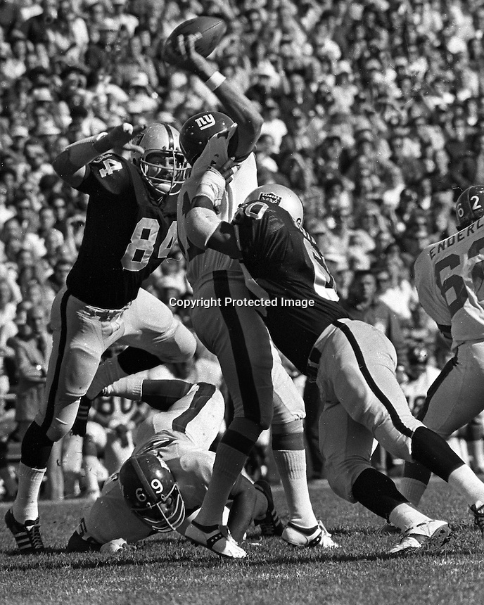 Oakland Raiders Tony Cline and Otis Sistrunk hit New York Giants quarterback (photo/Ron Riesterer)