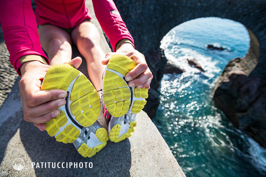 Stretching and warming up before a road run at Ponta do Sol on Madeira Island