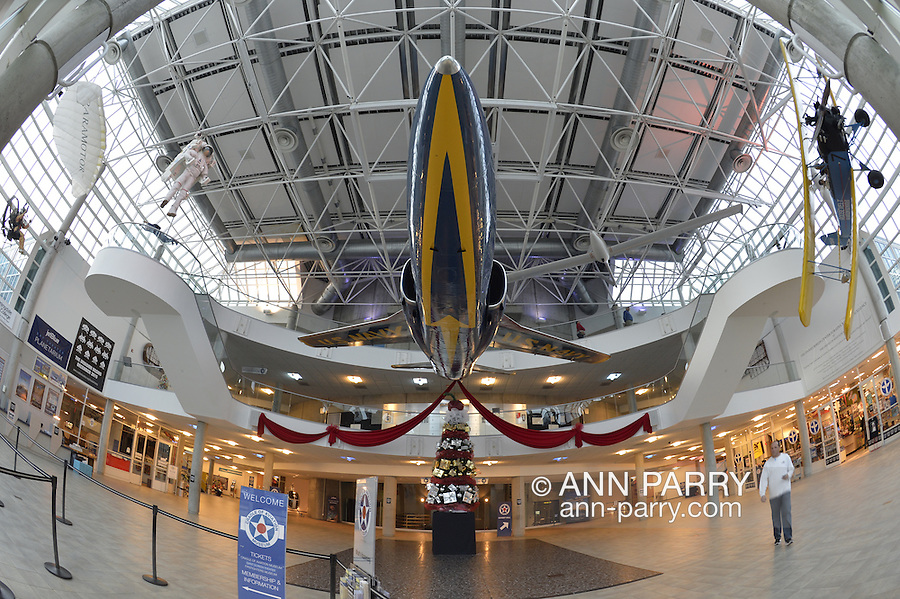 Garden City, New York, USA. December 12, 2015. Navy jet, suspended from ceiling of 3-story atrium, has long holiday red ribbons extending from it's rear, at  Cradle of Aviation Museum on Long Island.