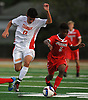 Jose Pena #13 of Chaminade (game-tying and game-winning goals, both in final minute of regulation), left, and Shawn Adams #5 of St. John the Baptist battle for possession during a NSCHSAA varsity boys soccer match played at St. John the Baptist High School on Tuesday, Sept. 11, 2018. Chaminade won by a score of 4-3.